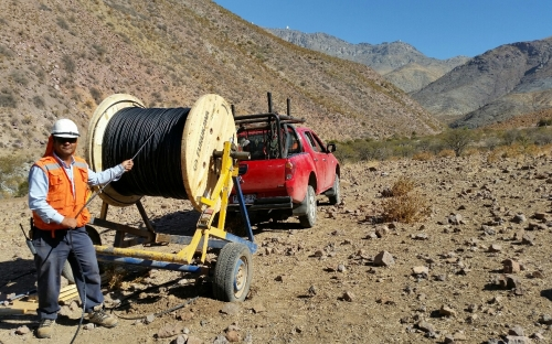 Again the backdrop of Cerro Pachón, a Telefonica/Cobra technician installs the AURA/LSST fiber optic cable from the AURA Gatehouse to the summit.  Telescopes on the summit, L-R, SOAR, Gemini-S, LSST.